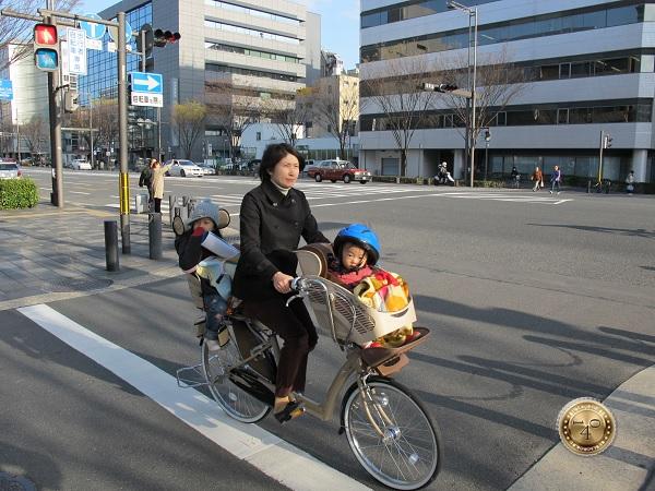 Мама с двумя детьми на велосипеде